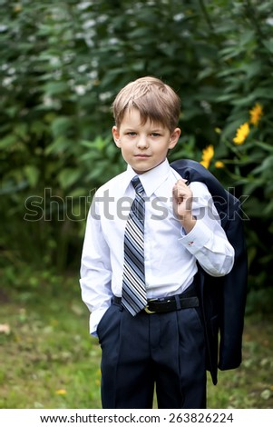 Portrait of little businessman on nature green background - stock photo