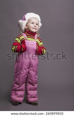 Portrait of Little Caucasian Girl in Winter Clothes Smiling and Looking Up. Against Gray Background. Vertical Image Composition - stock photo