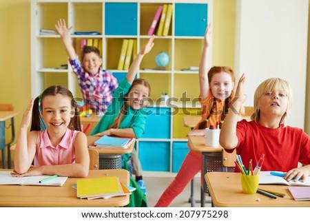 Portrait of little classmates raising hands at lesson - stock photo
