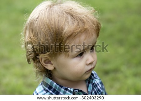 Portrait of little curious boy kid with blond curly hair in checkered blue shirt standing on green grass lawn looking away on natural background outdoor closeup, horizontal picture - stock photo