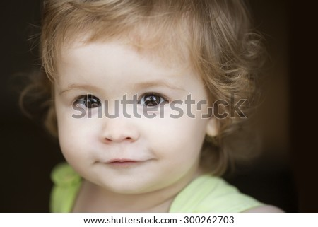 Portrait of little curious smiling male kid with blond curly hair looking forward outdoor on dark background, horizontal picture