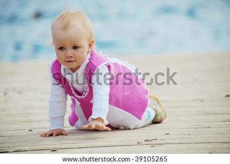 Portrait of little cute baby girl creeping on berth near sea - stock photo