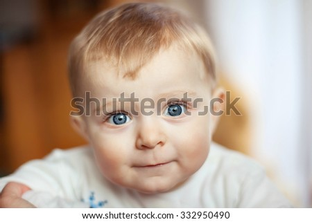 Portrait of little cute baby with blond hairs and big blue eyes. Happy carefree childhood. Kid looking at camera - stock photo