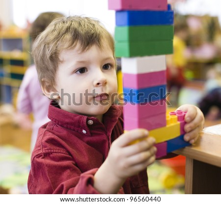 portrait of little cute boy making towel with lego - stock photo