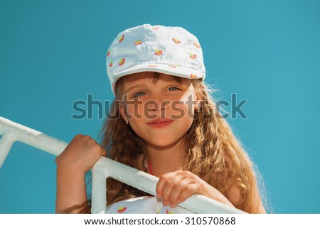 Portrait of little cute girl enjoying playing on boat on a hot sunny day - stock photo