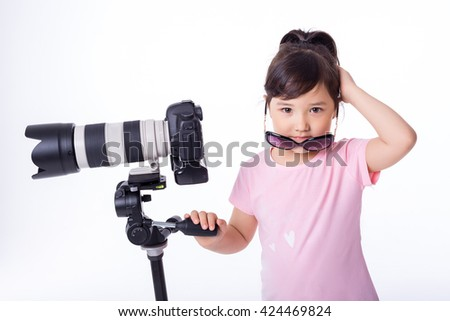 portrait of little cute girl holding a modern professional photo camera on tripod. child photographs