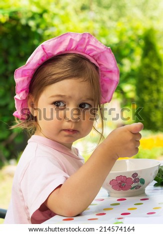 portrait of little cute girl in a purple cap eats with appetite a breakfast from a plate with the drawn flower in outdoor cafe  - stock photo