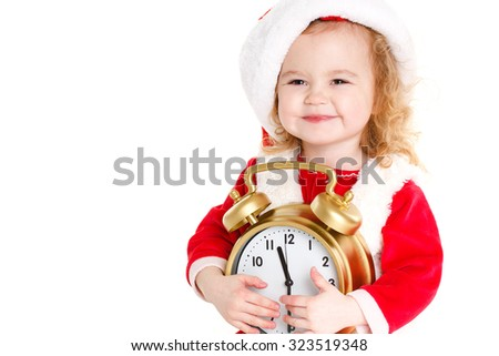 Portrait of little cute girl in santa hat holding big clock on white background. Christmas, winter, time and people concept - girl santa helper. Christmas santa child baby girl with clock - stock photo