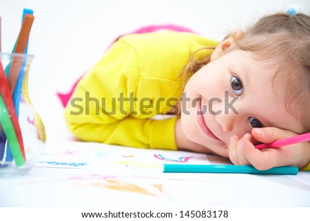 Portrait of little cute girl is drawing - stock photo