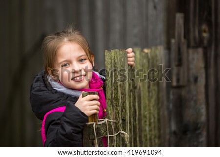 Portrait of little cute girl near the fence in the village.