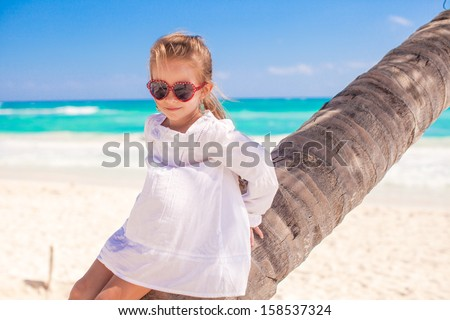 Portrait of little cute girl sitting on palm tree at the perfect caribbean beach - stock photo