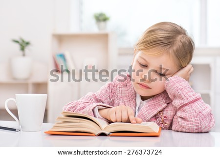 Portrait of little cute girl wearing pink suit. Girl sitting at table and sadly reading book. Room interior as a background - stock photo