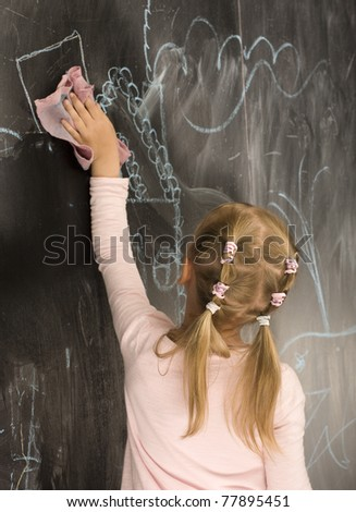 portrait of little cute girl with chalk writing on blackboard - stock photo