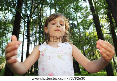 Portrait of little cute girl with curly blonde hair in white clothes inside green forest, she throws up hands, focus on face - stock photo