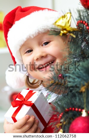 Portrait of little cute girl with  present  near Christmas tree - stock photo