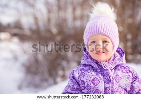 Portrait of Little cute happy girl in the snow sunny winter day