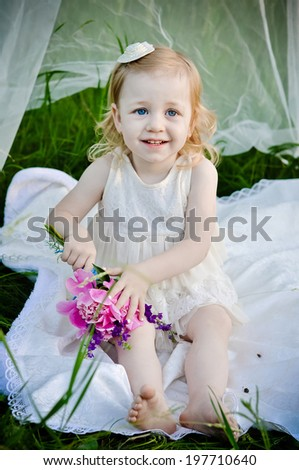 Portrait of little cute little, sitting at summer green park under the canopy  - stock photo