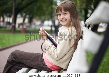 Portrait of little cute smiling girl schooler with open book is sitting  on the wooden bench in summer park - stock photo