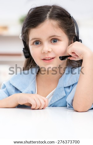 Portrait of little dark-haired girl playing role of business woman. Girl sitting at table with headphone. Office interior as a background. Concept for call centre - stock photo