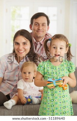 Portrait of little daughter standing in front at home while family smiling in background. - stock photo