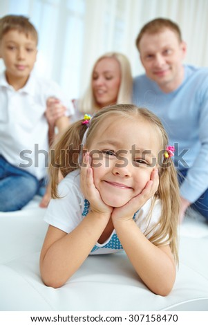 Portrait of little daughter with her family in the background - stock photo