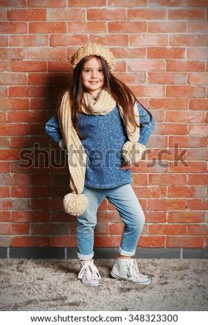 Portrait of little fashion kid girl on bricks wall background - stock photo