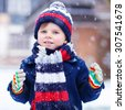 Portrait of little funny boy in colorful winter clothes having fun with snow, outdoors during snowfall. Active outdoors leisure with children in winter. Kid with hat, gloves and scarf with stripes.  - stock photo