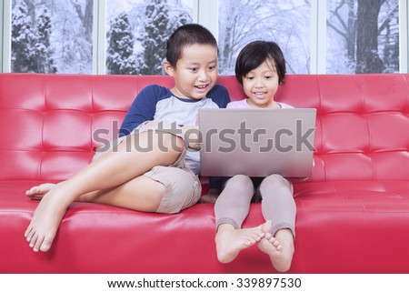 Portrait of little girl and her brother using laptop computer on the sofa at home - stock photo