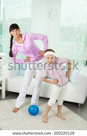 Portrait of little girl and her mother doing physical exercise at home