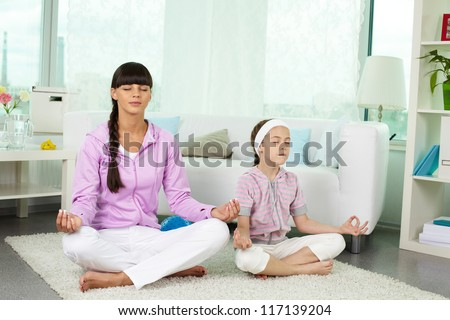 Portrait of little girl and her mother doing yoga exercise at home - stock photo