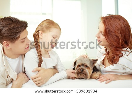 Portrait of little girl and her parents stroking a dog