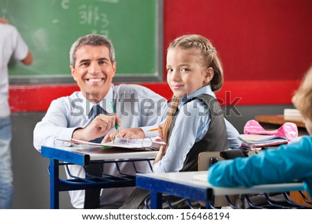Portrait of little girl and teacher sitting at desk in classroom