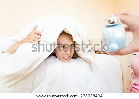 Portrait of little girl being was awakened by alarm clock - stock photo