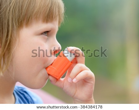 Portrait of little girl child  using asthma inhaler outdoors - stock photo