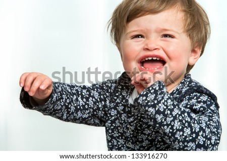 Portrait of little girl crying with arms raised. - stock photo