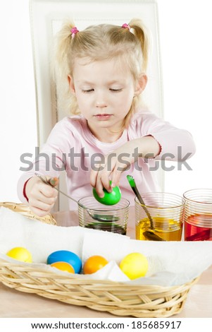 portrait of little girl during Easter eggs' coloration