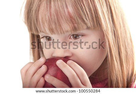 portrait of little girl eating apple close-up