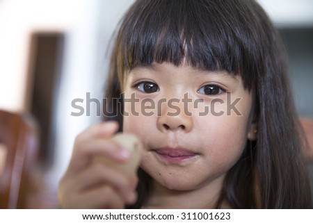 Portrait of little girl enjoy eating rambutan
