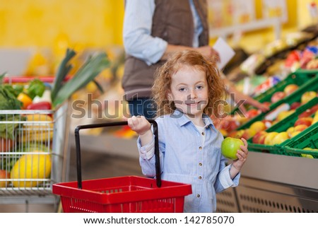 Portrait of little girl holding shopping basket and apple with woman in background at grocery store - stock photo