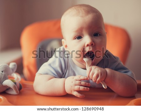 Portrait of little girl holding spoon - stock photo
