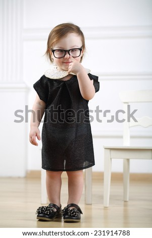 Portrait of little girl in black dress and glasses putting finger to nose - stock photo