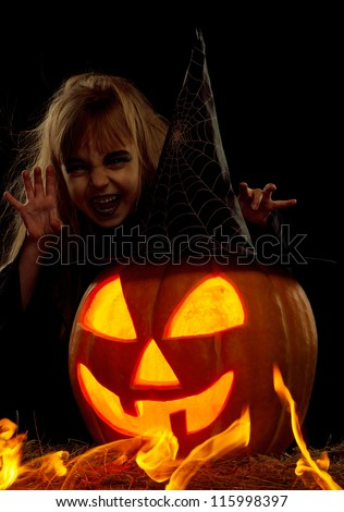 Portrait of little girl in black hat and black clothing with pumpkin on black background