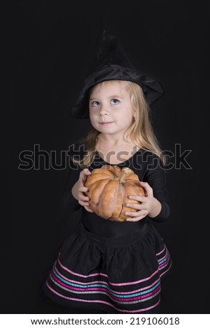Portrait of little girl in black hat and black clothing with pumpkin on black background  - stock photo