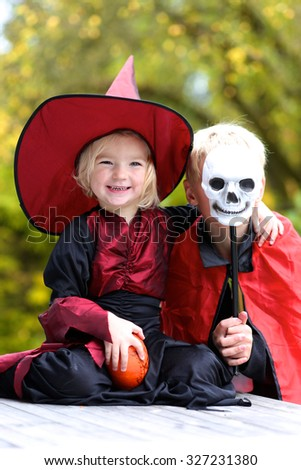 Portrait of little girl in Halloween witch costume and her teenage devil brother holding pumpkin and skull decoration - stock photo