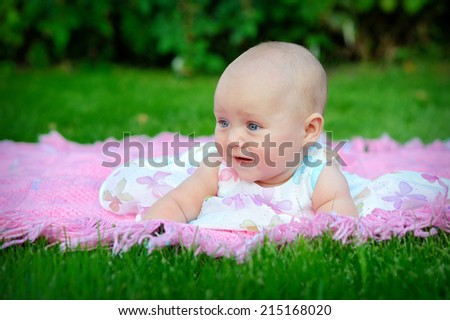 Portrait of little girl in the grass outdoors.  - stock photo