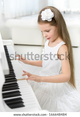Portrait of little girl in white dress playing piano. Concept of music study and art - stock photo