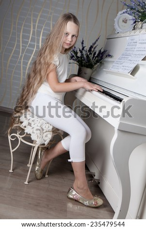 Portrait of little girl in white dress playing piano. Concept of music study and arts  - stock photo
