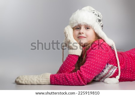 portrait of little girl in winter cap and mittens - stock photo