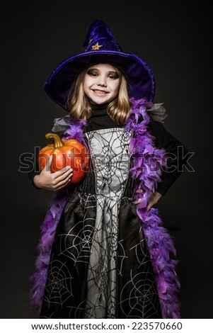 Portrait of little girl in witch costume with pumpkin. Halloween character. Studio portrait over black background    - stock photo