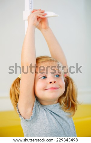 Portrait of little girl measuring herself. - stock photo